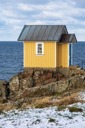 A small yellow wooden house during winter in the seaside village of Torekov situated on the Swedish west coast. Selective focus.