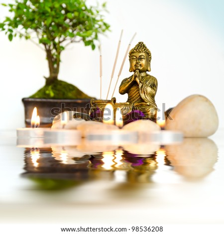 A small zen altar surrounded by candles and bonsai, is reflected in water