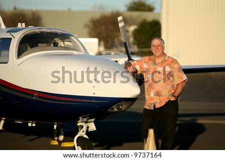 a smart and well to do man stands proudly next to his latest airplane for his photo