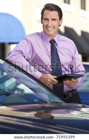 A smart businessman leaning on his car outside with a tablet computer