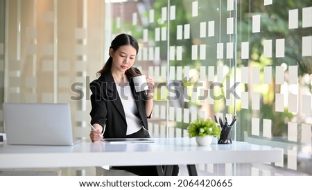 A smart confident young asian business woman drinking coffee during working on tablet computer in the modern office.