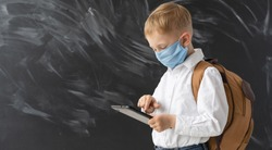A smart modern schoolboy in a protective mask is standing near the school board. Quarantine education. Primary school education in a pandemic. The boy holds a tablet in his hands and smiles. Place for