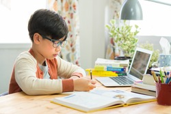 A smart preteen boy sitting at the table, writing homework or preparing for the exam. Teen using notebook computer to study. Student, School, Remote, Online learning, New normal, Home Based Learning.