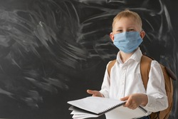 A smart schoolboy is standing near the school blackboard. There is a protective mask on his face. In the hands of the boy is a large notebook for writing. On the back is a brown schoolbag. Quarantine