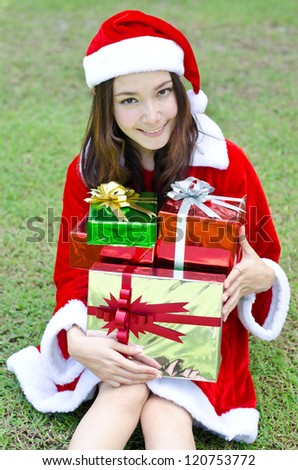 A Smiley Asian santa woman with box gifts sit on green field.