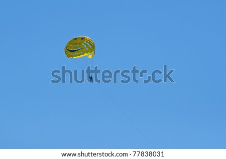 A smiley face yellow parasail in mid air over the ocean