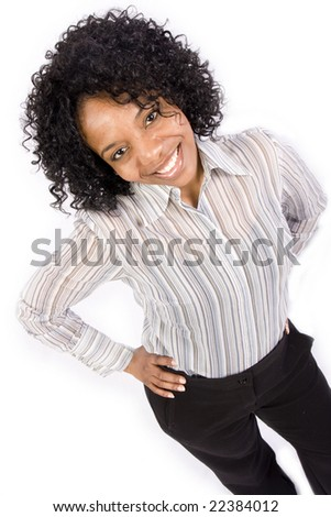 A smiling african american female looks at the camera with her hands on her hips in front of an isolated white backdrop