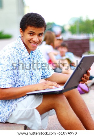 A smiling african american man on his laptop