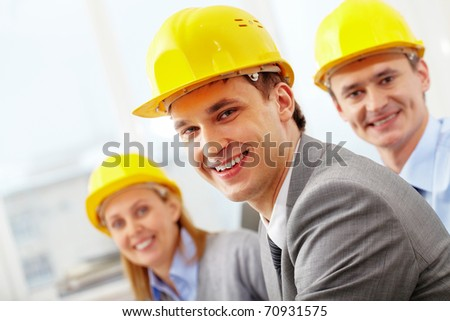 A smiling architect in helmet against his two colleagues