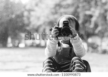 a smiling Asian girl take photos with a digital camera before a picture windows. black and white. background for design