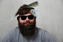 A smiling bearded man in black glasses with money on his head. Dollar bills in the head of a man A man with a beard and sunglasses on a gray background. Concept: Business, finance. Humor. Joke.