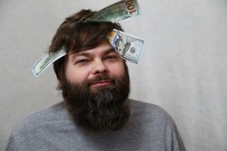 A smiling bearded man with a shock of hair and money on his head. Dollar bills in the head of a man with a beard on a gray background. Concept: A man thinks about money. Business, finance. Humor. Joke
