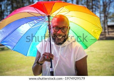 A smiling bisexual black man living with HIV holding a colorful rainbow umbrella on a sunny day Stockfoto ©