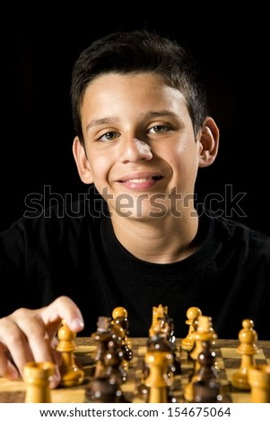 a smiling boy during a chess game.