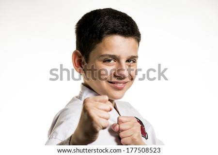 A smiling boy with his fist up in a karate fight stance.
