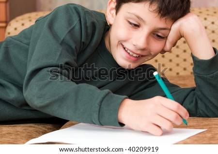 a smiling boy writes a letter on the sofa