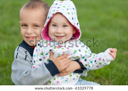 A smiling brother is sitting on the green grass and hugging his little sister