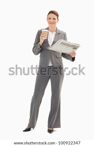 A smiling businesswoman is holding a cup and a newspaper