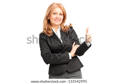 A smiling businesswoman leaning on wall and giving a thumb up isolated on white background