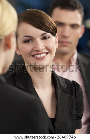 A smiling businesswoman meeting and greeting her female colleague while out of focus behind her is her male colleague