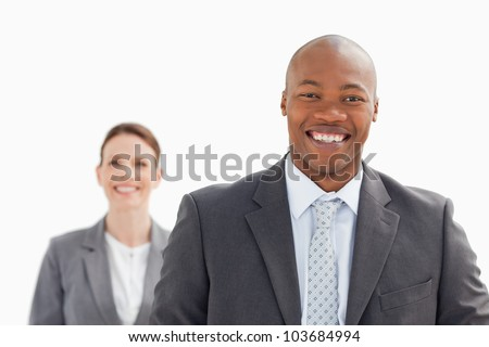 A smiling businesswoman stands behind smiling business man