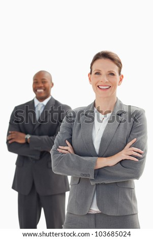 A smiling businesswoman stands in front of smiling businessman