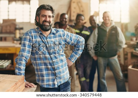 A smiling carpenter with his staff in the background