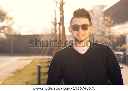 A smiling casually dressed young successful man at sunrise in the city town.