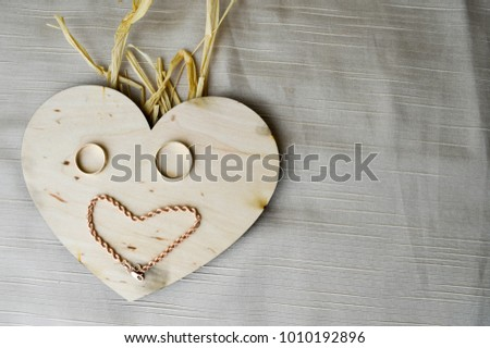 A smiling, cheerful, kind face with straw hair made from a wooden heart to Valentine's Day, wedding gold rings and a female gold chain on a beige background. #1010192896