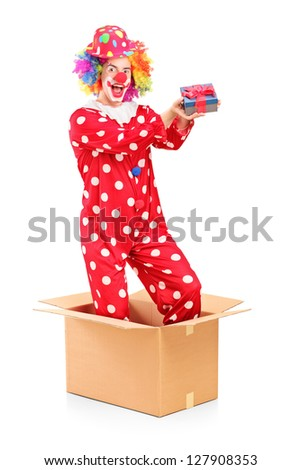 A smiling clown in a cardboard box holding a gift isolated on white background