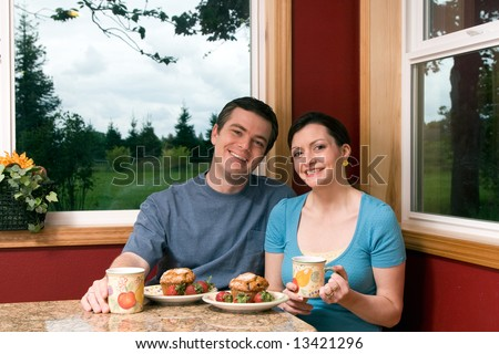 A smiling couple eating continental breakfast at home. - stock photo