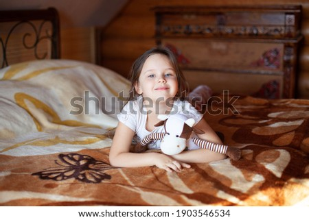 a smiling, cute girl hugs a toy cow and lies on a sunny morning on a bed in the bedroom of a rustic log house. Stock photo ©