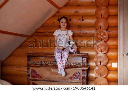 a smiling, cute little girl sits on an old wooden dresser and hugs a toy cow in the bedroom of a rustic log house. Stock photo ©