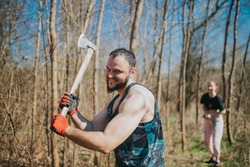 A smiling dangerous  horrible robust caucasian man in the forest ax in hand ready to strike,  looking at the camera, a woman in the background