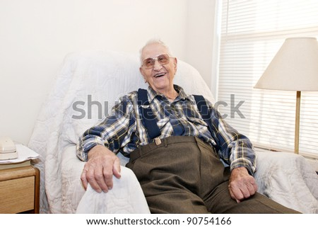 A smiling elderly man sitting in a chair in his apartment