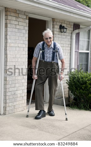 A smiling elderly man with crutches standing outside of his apartment