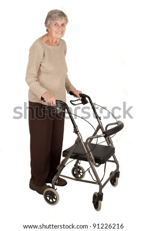 A smiling elderly woman standing with her walker isolated on white background