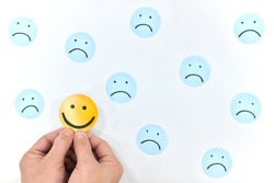 A smiling face icon among a group of sad emoticons in white background. Be positive and stay happy concept.