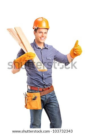 A smiling female carpenter holding sills and giving thumb up isolated on white background