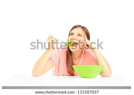 A smiling female eating salad isolated against white background