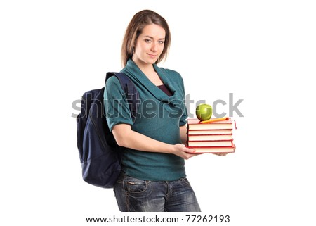 A smiling female student holding books and an apple isolated on white background