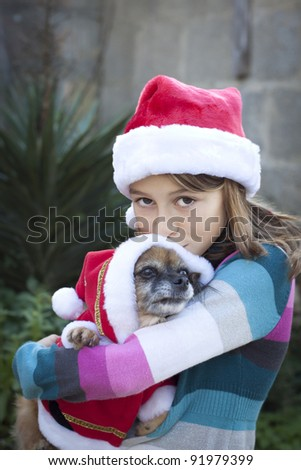 A smiling girl in santa hat holding a small dog in a santa costume