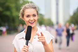 A smiling girl reporter with microphone in hand on the street