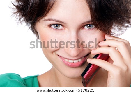 A smiling girl speaks by a mobile phone