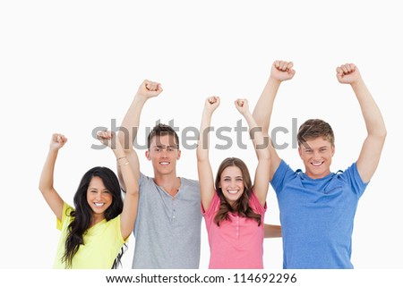 A smiling group as they celebrate with their hands raised in the air