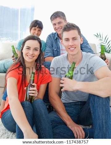 A smiling group of friends as one couple sit on the floor and the other couple sit on the couch with beers