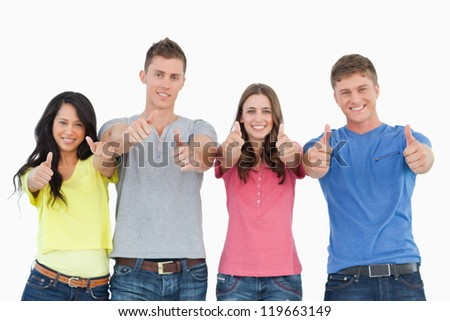 A smiling group of friends give a thumbs up while looking at the camera - stock photo