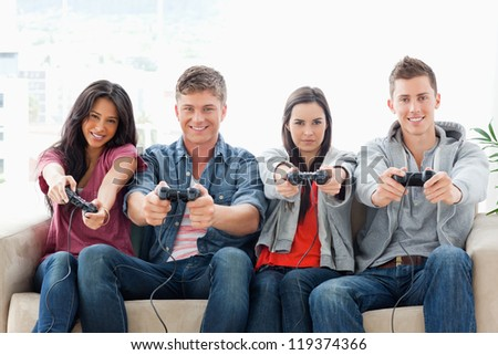 A smiling group of friends sit on the couch together while playing a game with controllers