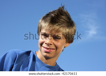 a smiling handsome 10-years old boy with a fashionable hairstyle photographed in the summer sun with blue sky and tiny clouds in the background