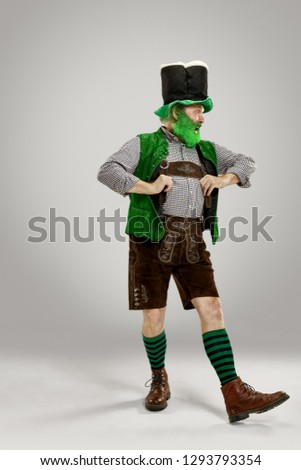 A smiling happy senior man in a leprechaun hat with beard at studio. He celebrates St. Patrick's Day. The celebration, festive, beer, holiday, alcohol, party concept